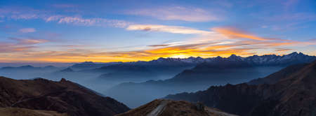 expansive: Colorful sunset behind majestic mountain peaks of the Italian Alps. Fog and mist covering the valleys below, autumnal landscape, cold feeling. Stunning sky. XXXL expansive panorama.