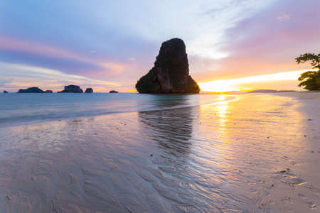 Low tide with a vibrant colored sunset in the majestic scenery of Railey Bay, Krabi