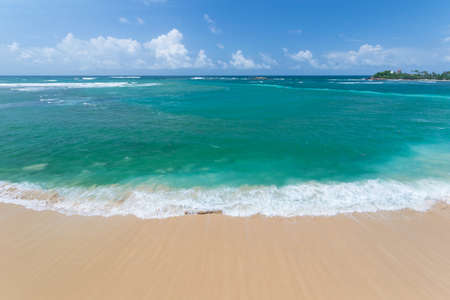 expansive: Expansive view from above of the awesome greenish turquoise waving ocean and the golden Unawatuna beach Stock Photo