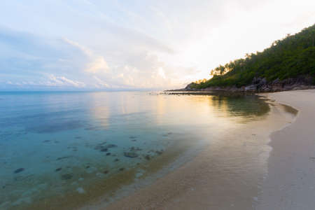 tourist resort: Golden sunrise on desert sandy exotic beach surrounded by lush green jungle. Summer adventures in tourist resort on the remote Bottle Beach, Koh Phangan, Thailand, famous travel destination. Expansive view, natural colors. Stock Photo