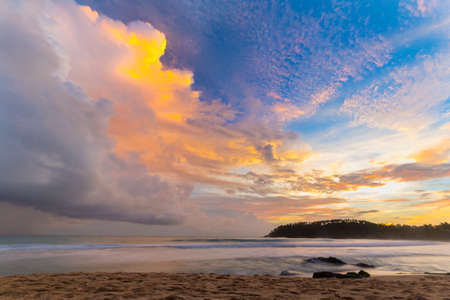 Golden sunset on desert beach with colorful sky and scenic cloudscape during monsoon time.