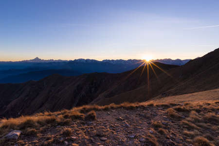 expansive: High altitude mountain range at sunset with glowing grass in the foreground. Shot in backlight with star shaped sun in the italian Alps. Expansive view, mountain silhouette.