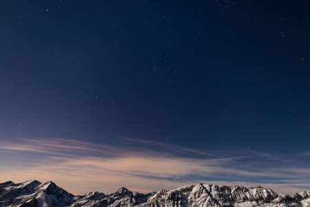 moonlight: The starry sky captured on the Alps in winter. The Pleiades, Orion Constellation, Betelgeuse and Sirio star clearly visible. Snowcapped mountain ridge glowing under moonlight. Low digital noise.
