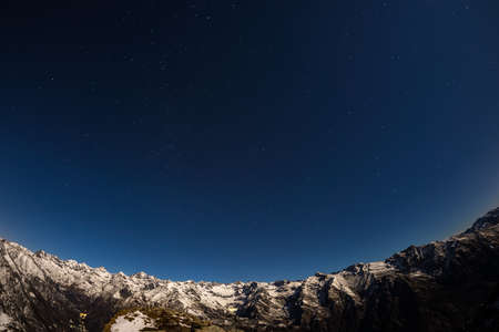 soul searching: The starry sky captured on the Alps by fisheye lens. Gran Paradiso National Park snowcapped mountain range glowing under moonlight. Cassiopeia, Andromeda and The Great Bear constellation (Ursa Major or the Big Dipper) clearly visible. Low digital noise. I