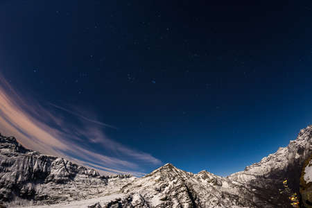 soul searching: The starry sky captured on the Alps by fisheye lens. Gran Paradiso National Park snowcapped mountain range glowing under moonlight. Cassiopeia, Andromeda, The Pleiades, Orion Constellation, Betelgeuse and Sirio.