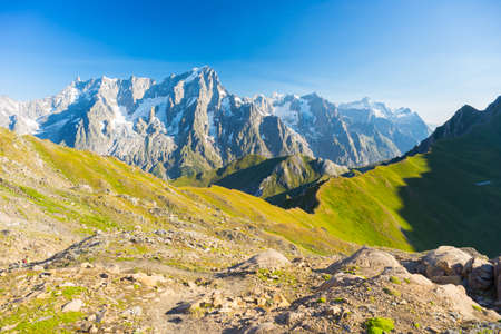 majestic: Hih mountain trail with great panoramic view over the Mont Blanc massif. Backpackers summer adventures and wanderlust in Valle dAosta, Italian French Alps. Stock Photo