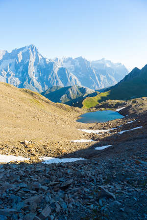 wanderlust: High mountain trail with great panoramic view over the Mont Blanc massif and blue lake. Backpackers summer adventures and wanderlust in Valle dAosta, Italian French Alps. Stock Photo