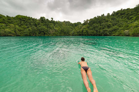 the one person: One person diving into the turquoise water of the remote Togean or Togian Islands, Central Sulawesi, Indonesia. Scenic lush green rainforest surrounding the transparent blue lagoon. Blurred motion. Stock Photo