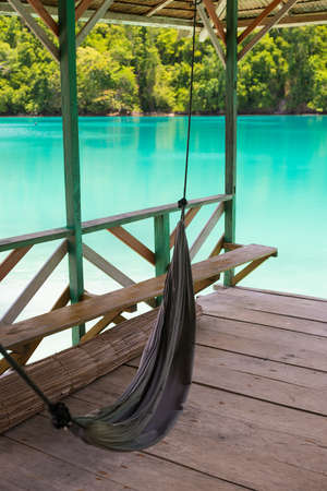tourist resort: Hanging hammock for relax in tropical tourist resort on the remote Togean Islands, Central Sulawesi, Indonesia. Scenic turquoise sea and lush green forest.