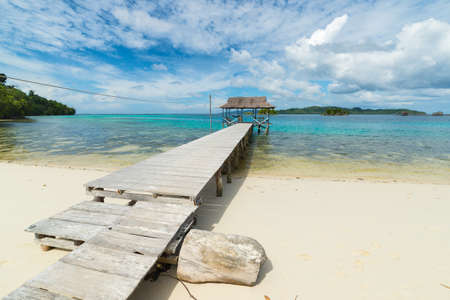 Wooden jetty crossing scenic turquoise see in tourist resort on desert island. Summer adventures on the remote Togian (Togean) Islands, Central Sulawesi, Indonesia.