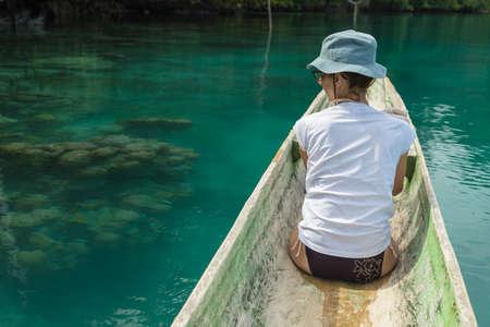 ocean kayak: remar Turista en canoa tradicional de madera en laguna azul a lo largo de la costa salvaje de Malenge, en las remotas Islas Togean, Sulawesi, Indonesia. enfoque selectivo.