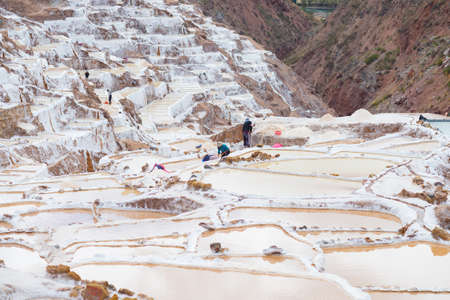 manual work: Maras, Peru - September 5, 2015: Workers, mostly women and girls, manually extracting minerals from terraced salt pans in Maras, Urubamba Valley, Peru. Concept of manual work in developing countries. Stock Photo