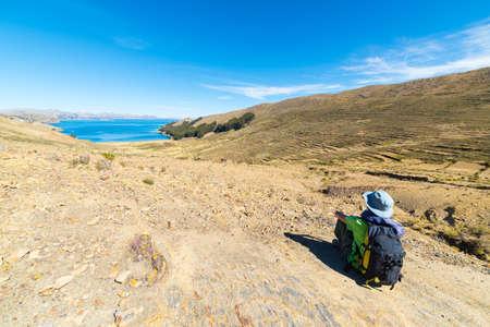 mujer mirando el horizonte: Backpacker turística sentado y mirando a la majestuosa vista expansiva desde arriba en la Isla del Sol, Lago Titicaca, escénico destino del viaje en Bolivia. aventuras y vacaciones viajar en las Américas.