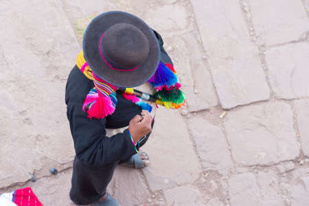 directly above: Taquile, Peru - September 1, 2015: Directly above view of traditionally dressed man in Taquile Island, Titicaca Lake, Peru. About 2200 people live on the island. They speak Quechua language.
