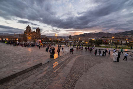 peru: Cusco, Peru - September 2, 2015: People on main square, Plaza de Armas, with facade of church in Cusco, Peru, former Inca capital, famous travel destination in the world. Night view.