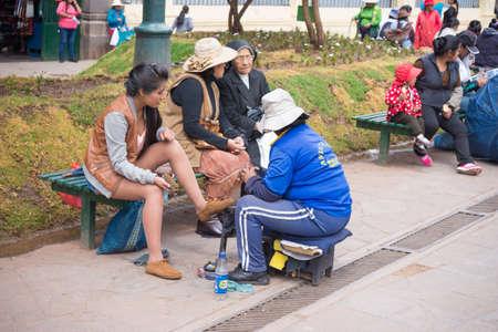 peruvian ethnicity: Cusco, Peru - September 3, 2015: Shoeshiner working with a female client in the streets of Cusco, Peru. Editorial