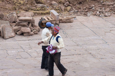 peruvian ethnicity: Taquile, Peru - September 1, 2015: Traditionally dressed men at work in Taquile Island, Titicaca Lake, Peru. About 2200 people live on the island. They speak Quechua language.