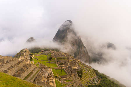 dreamlike: Machu Picchu illuminated by the first soft sunlight coming out from the opening clouds. Mist, clouds and fog composing an idyllic and dreamlike frame. The Incas city is the most visited travel destination in Peru.