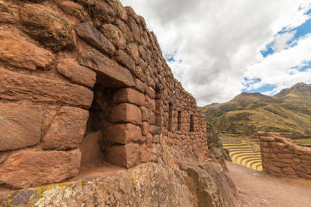 cusco region: Wide angle view of the glowing majestic concentric terraces of Pisac, Incas site in Sacred Valley, major travel destination in Cusco region, Peru. Stone wall in the foreground.