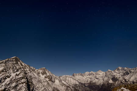 ursa minor: The starry sky captured on the Alps. Gran Paradiso National Park snowcapped mountain range glowing under moonlight. Low digital noise. Italy.