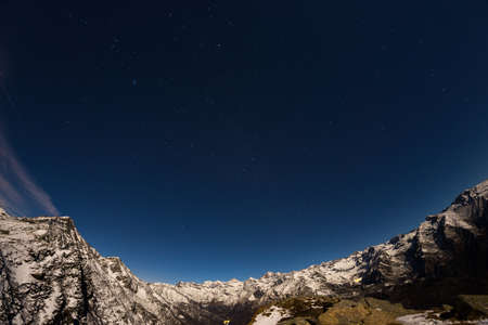 ursa minor: The starry sky captured on the Alps by fisheye lens. Gran Paradiso National Park snowcapped mountain range glowing under moonlight. Cassiopeia, Andromeda and The Great Bear constellation (Ursa Major or the Big Dipper) clearly visible. Low digital noise. I