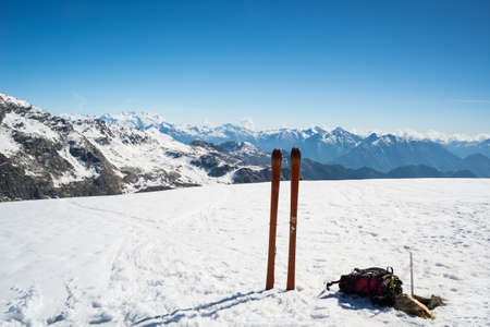 conquering adversity: Ski tour equipment with climbing skin and backpack in scenic high mountain backgrounds in the Italian French Swiss Alps. Monte Rosa Massif at the horizon.