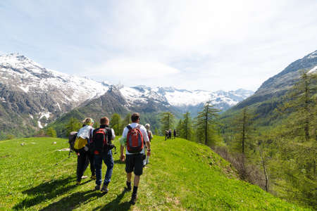 expansive: Courmayeur, Italy - May 10, 2015: Group of hikers walking on mountain trails with expansive view over the Alps, Courmayeur, Italy. Outdoor activities and wanderlust in summer - spring.