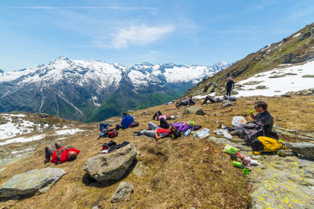 expansive: Group of hikers resting on mountain summit with expansive view over the Alps, Courmayeur, Italy. Outdoor activities and wanderlust in summer - spring.