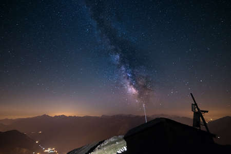the french way: The outstanding beauty of the Milky Way and the starry sky captured at high altitude in summertime on the italian french Alps with glowing Aosta Valley below. Wide angle view, some acceptable digital noise and grain due to long exposure and high iso setti Stock Photo