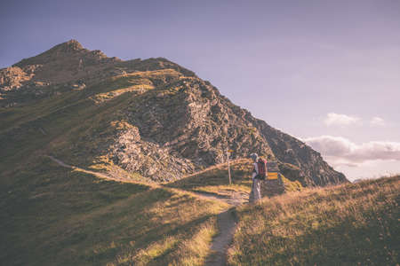 the one person: One person hiking uphill on footpath in the italian Alps with panoramic view on the mountains. Summer adventures and exploration on the Alps. Toned image, vintage filter style, vignetting added.