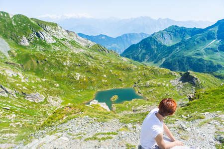 expansive: Red hair woman sitting on the mountain summit and looking at blue lake and expansive panorama of high mountain range of the Italian Alps. Summer adventures and exploration in Gran Paradiso National Park. Wide angle view from above.