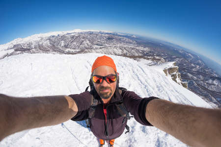fisheye: Adult alpin skier with beard, sunglasses and hat, taking selfie on snowy slope in the beautiful italian Alps with clear blue sky. Concept of wanderlust and adventures on the mountain. Wide angle fisheye lens.