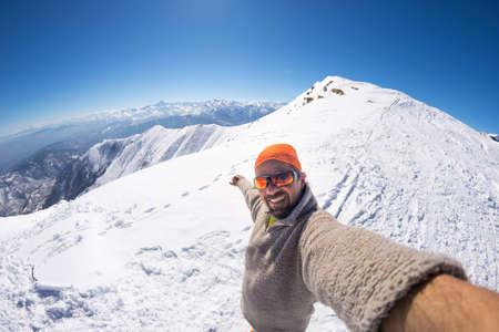 Volwassen alpine skiër met baard, zonnebril en hoed, waarbij selfie op besneeuwde helling in de prachtige Italiaanse Alpen met duidelijke blauwe hemel. Concept van de reislust en avonturen op de berg. Groothoek fisheye lens. Stockfoto