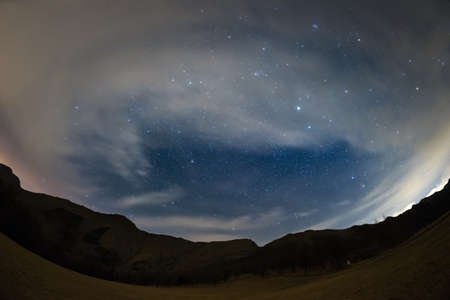 soul searching: 180 degree view of the starry sky and Milky Way on the Alps, with blurred motion clouds drawing scenic vortex due to fisheye lens distortion. Some digital noise due to 1600 iso setting. Stock Photo