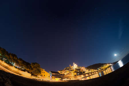 soul searching: The starry sky captured on the coastline and historical town of Cervo, Ligurian Riviera, famous travel destination in Italy, glowing under moonlight. Scenic distortion by fisheye lens.