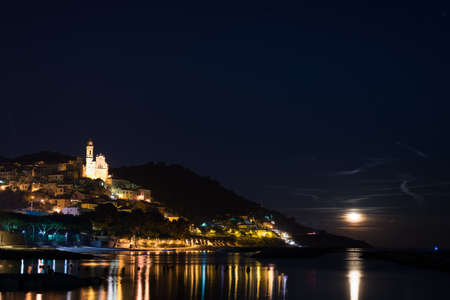 soul searching: The historical town of Cervo glowing in the night nder moonlight and starry sky on the coastline of Ligurian Riviera, famous travel destination in Italy.