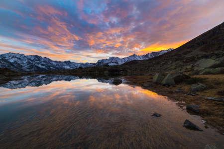 Hooggelegen bergmeer in idyllisch land ooit bedekt door gletsjers. Weerspiegeling van besneeuwde bergen en schilderachtige kleurrijke hemel bij zonsondergang. Groothoek schot genomen op de Italiaanse Alpen op 2200 m boven zeeniveau.