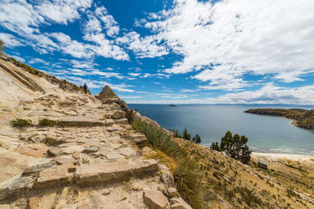 the one person: Panoramic Inca trail on Island of the Sun, Titicaca Lake, among the most scenic travel destination in Bolivia. Travel adventures and vacations in the Americas. One person walking in the distance. Stock Photo