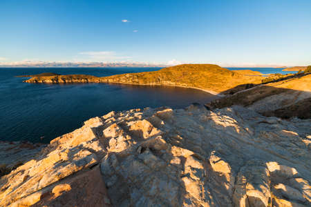 expansive: Sunset light on the Island of the Sun, Titicaca Lake, among the most scenic travel destination in Bolivia. Expansive panorama with glowing rocks in the foreground.