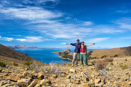 outstretched arms: Couple of tourist with outstretched arms looking at camera on the Island of the Sun, Titicaca Lake, Bolivia. Concepts of wanderlust and people traveling around the world. Expansive view.