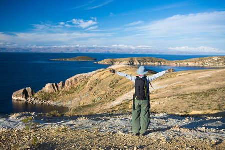 outstretched arms: Tourist with outstretched arms on Inca trail at the Island of the Sun, Titicaca Lake, Bolivia. Concepts of wanderlust and people traveling around the world. Expansive view. Stock Photo
