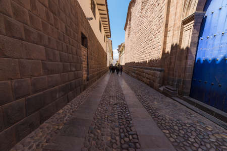 inca architecture: Narrow alley in the center of Cusco, Peru, former Inca capital, famous travel destination in the world, a mix of Inca and colonial architecture. Unrecognizable people walking ahead.