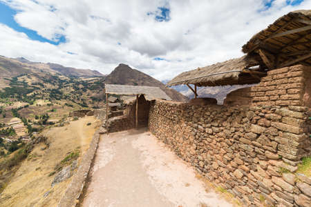 expansive: Expansive view of the Sacred Valley, Peru from Pisac Inca site, major travel destination in Cusco region, Peru. Stone wall in the foreground, dramatic sky.