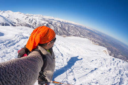 touring: Adult alpin skier with beard, sunglasses and hat, taking selfie on snowy slope in the beautiful italian Alps with clear blue sky. Concept of wanderlust and adventures on the mountain. Wide angle fisheye lens.