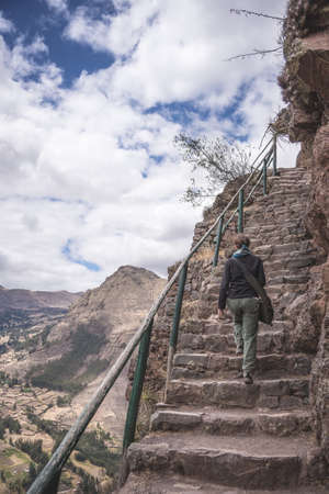 expansive: Tourist exploring the majestic steep Inca Trails inside the ruins of Pisac, Sacred Valley, major travel destination in Cusco region, Peru. Expansive view from above, Desaturated image.