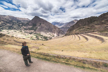 expansive: Tourist exploring the Inca Trails leading to the ruins of Pisac, Sacred Valley, major travel destination in Cusco region, Peru. Expansive view from above, Desaturated image.