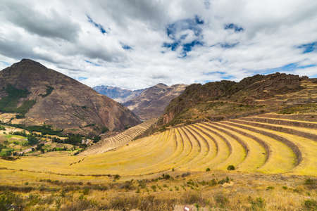 pisac: Expansive view of the glowing majestic concentric terraces of Pisac, Incas site in Sacred Valley, major travel destination in Cusco region, Peru. Dramatic sky. Stock Photo