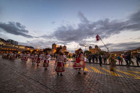 plaza de armas: Cusco, Peru - September 2, 2015: Group of peruvian people performing traditional dancing and public parade in Plaza de Armas, Cusco, Peru. Dusk time, blurred motion. Editorial