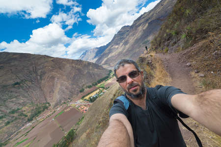 expansive: Fellow traveler taking selfie while visiting Inca site of Pisac, Sacred Valley, major travel destination in Cusco region, Peru. Expansive view. Stock Photo