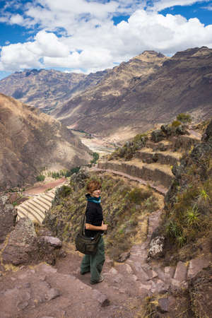 pisac: Tourist exploring the Inca Trails leading to the ruins of Pisac, Sacred Valley, major travel destination in Cusco region, Peru. Vacations and adventures in South America.